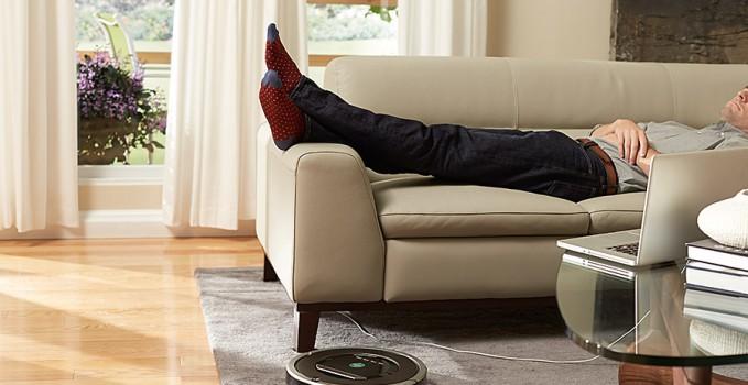 Staubsaugroboter Roomba 870 bei der Arbeit, während im Hintergrund ein Mensch auf einem Sofa liegt.