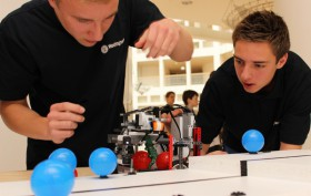 Zwei Jugendliche arbeiten an einem LEGO-Roboter.