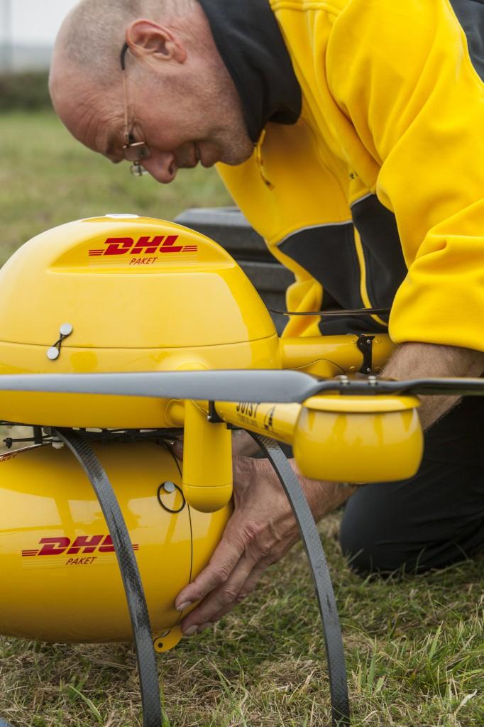 Nach der Ankunft auf Juist entnimmt ein DHL-Mitarbeiter die Ware des Paketkopters
